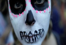 A woman demonstrates against Brazil's congressional move to criminalize all cases of abortion, including cases of rape and where the mother's life is in danger, with a face painting representing a woman dead after an illegal abortion, in Rio de Janeiro